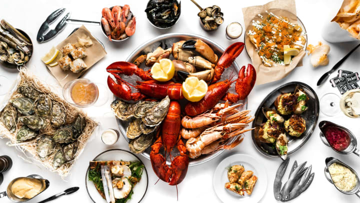 Cooked crawfish and assorted other seafood photographed from above on a white table top.