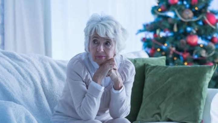 Woman sitting on couch with Christmas tree in background