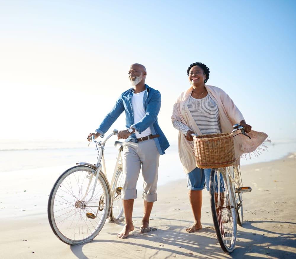 Residents walking their bikes along the beach near Carmel Village in Fountain Valley, California