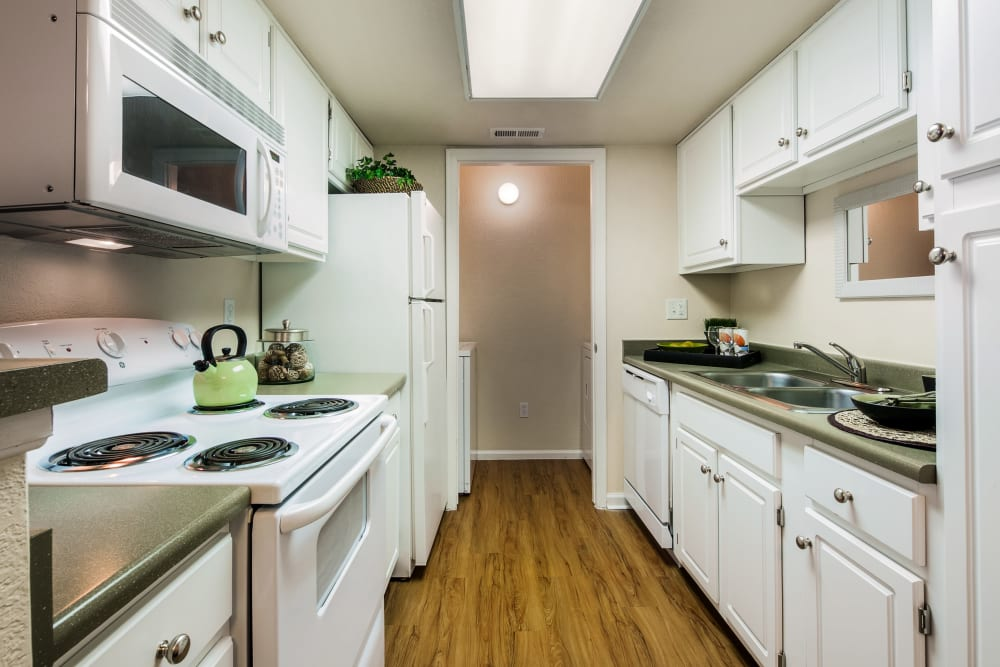 White appliances and cabinetry in a model home's kitchen at Waterfield Court Apartment Homes in Aurora, Colorado