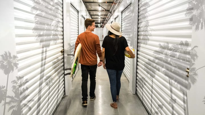 Man carrying surfboard and woman carrying a volleyball walk through a self storage corridor