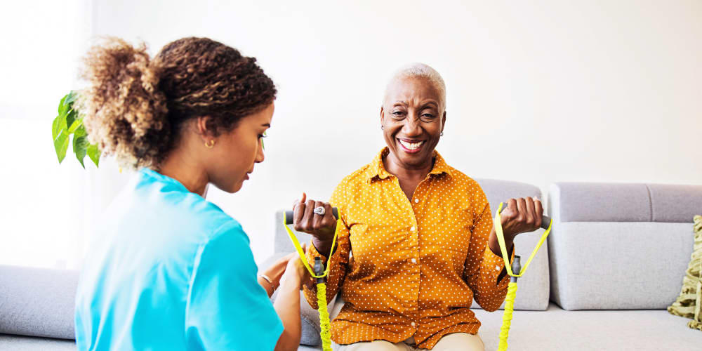 A staff member helping a resident stretch at Careage Home Health in Bellevue, Washington.