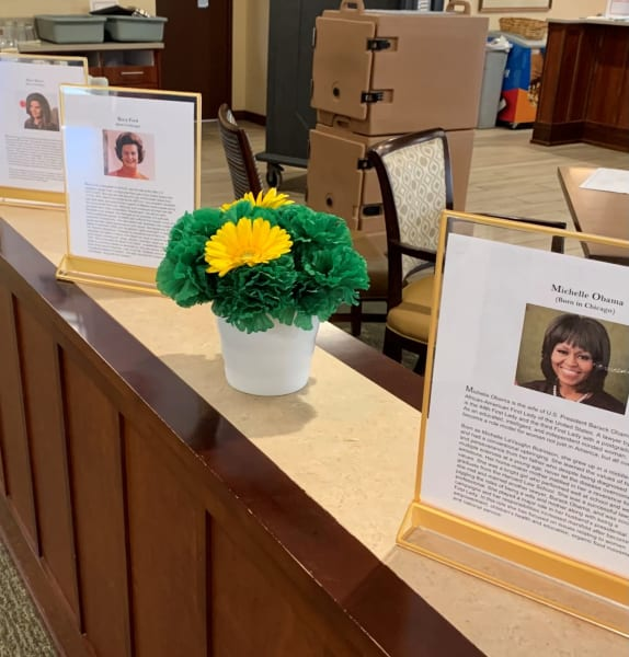 Women's History Month bios and photos displayed on the counters.