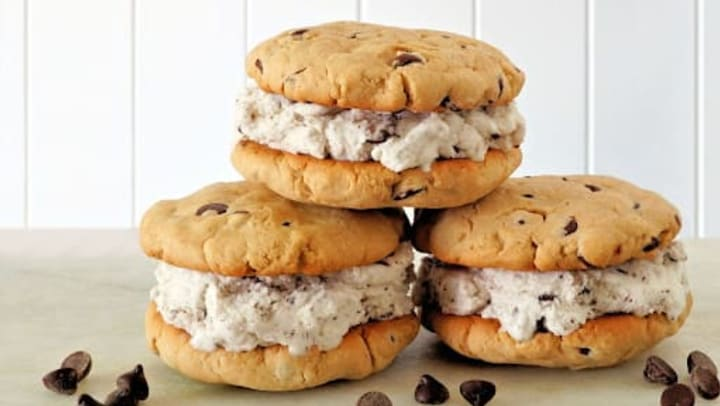Chocolate chip cookie ice cream sandwiches against a white background.