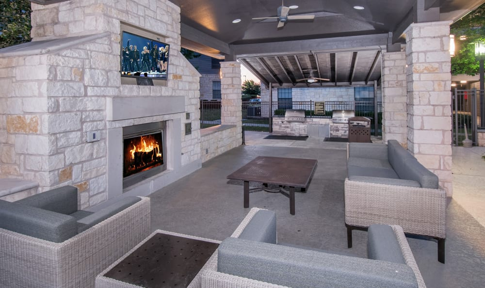Outdoor lounge with fireplace and large screen television at Villas Tech Ridge in Pflugerville, Texas