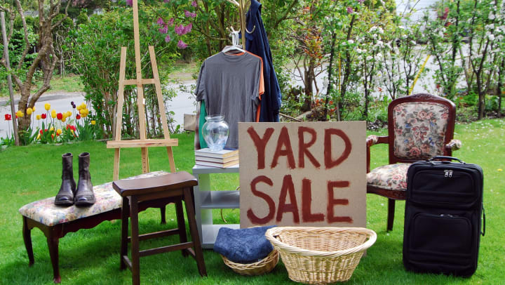 Items on a green lawn with a sign that says yard sale.