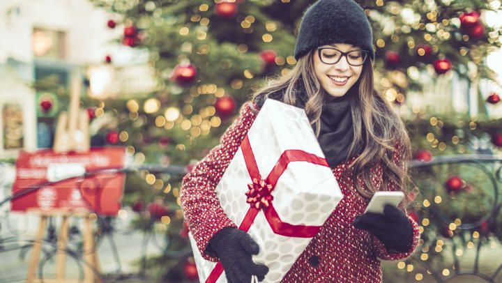 A warmly dressed young woman carrying a shopping bag and a wrapped holiday gift glances at her phone.