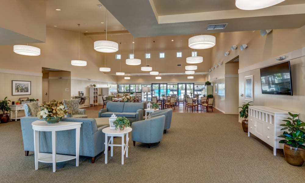 Common space with large chairs and sofas at Merrill Gardens at Rancho Cucamonga in Rancho Cucamonga, California.