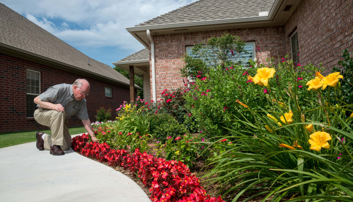 A resident smelling the flowers at Touchmark at Coffee Creek in Edmond, Oklahoma