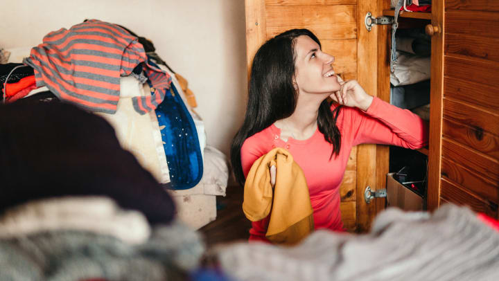 Woman sits outside her closet, sorting out her wardrobe.