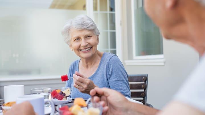 Senior woman smiling looking at a senior man while eating fruit.