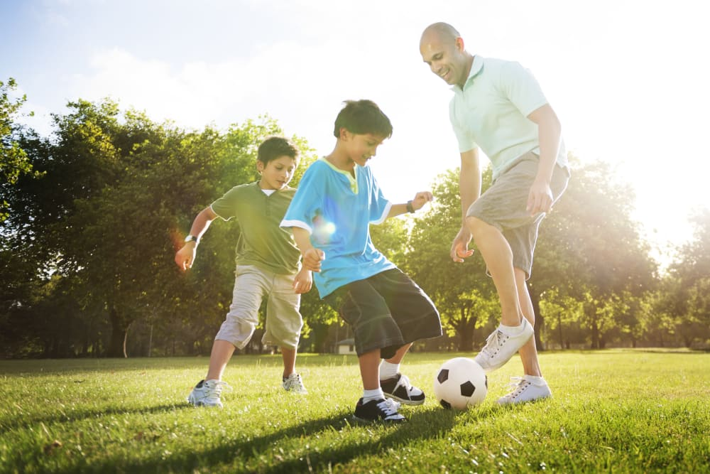 Family playing soccer on the green grass at TerraLane at Canyon Trails in Goodyear, Arizona