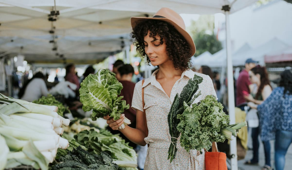 Resident shopping for fresh produce at a farmers market near Villa Vicente in Los Angeles, California