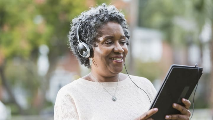 A smiling older woman is wearing headphones and holding a table while listening to an audiobook.