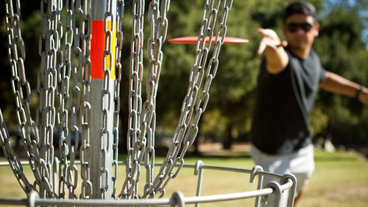 Man throwing a disc golf toward a basket near Cactus Forty-2 in Phoenix, Arizona