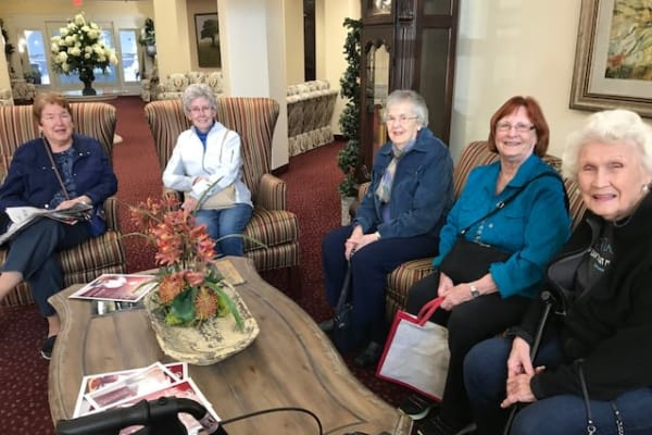 Residents on comfortable couches posing for a photo at Ashton Gardens Gracious Retirement Living in Portland, Maine