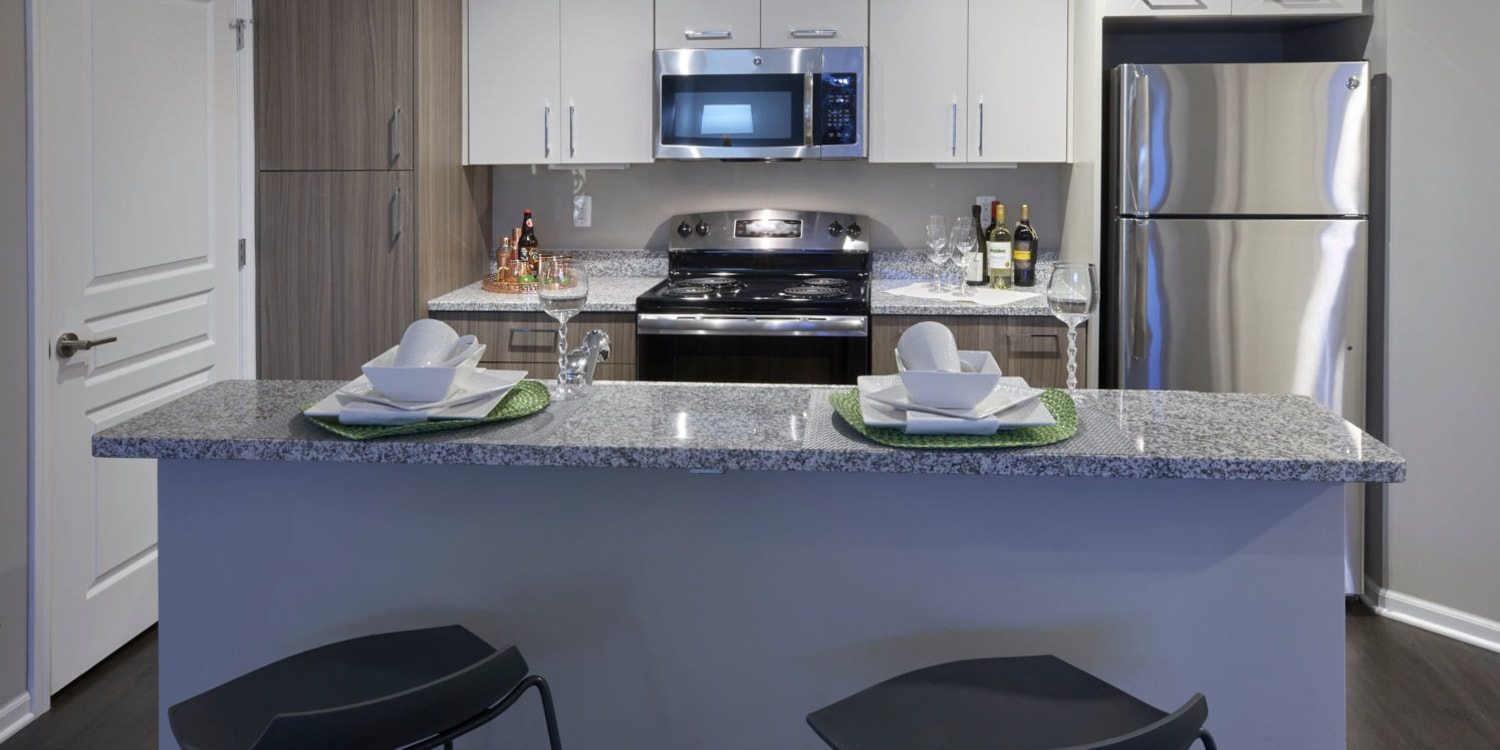 Granite countertops and stainless-steel appliances in a model home's kitchen at Uptown Ann Arbor in Ann Arbor, Michigan