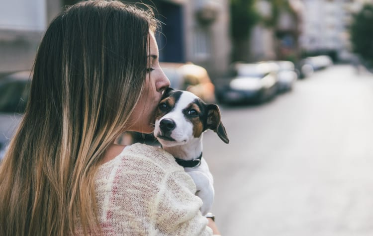 Resident giving her puppy a kiss outside their new home at Sofi Canyon Hills in San Diego, California
