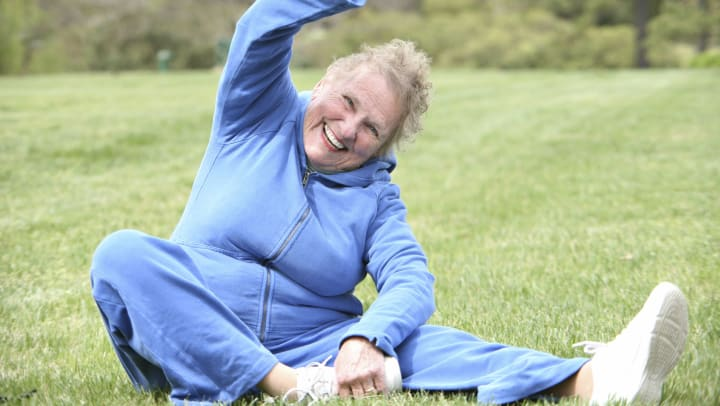 Image of a woman stretching on the grass in her yard.