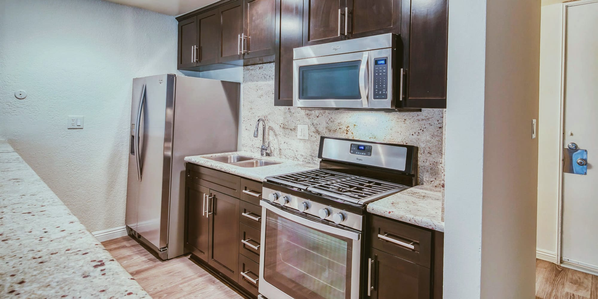 Hardwood flooring and stainless-steel appliances in a model apartment's kitchen at Mediterranean Village in West Hollywood, California