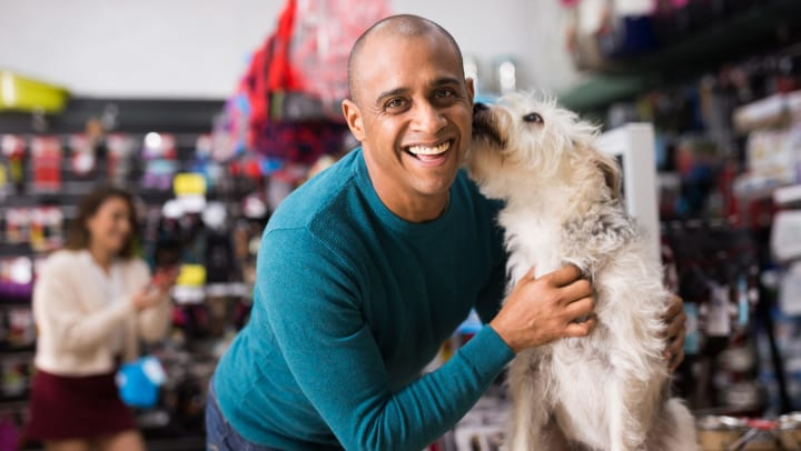 Smiling man with hands on small dog that's standing on a table and licking the man's neck.