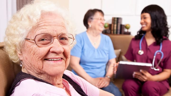 Female senior smiling while a caregiver is meeting with a resident in the background.
