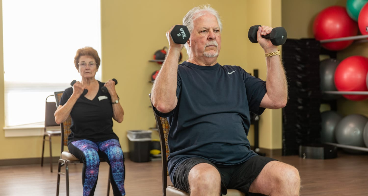 Two seated club members lifting weights at Touchmark on West Century Health & Fitness Club in Bismarck, North Dakota