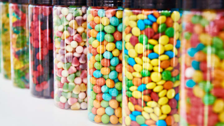Brightly colored candies stored in clear glass jars on a shelf.