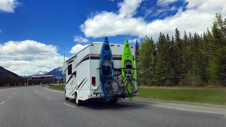 An RV with two kayaks and a bike on the back moving along a highway with mountains in the background