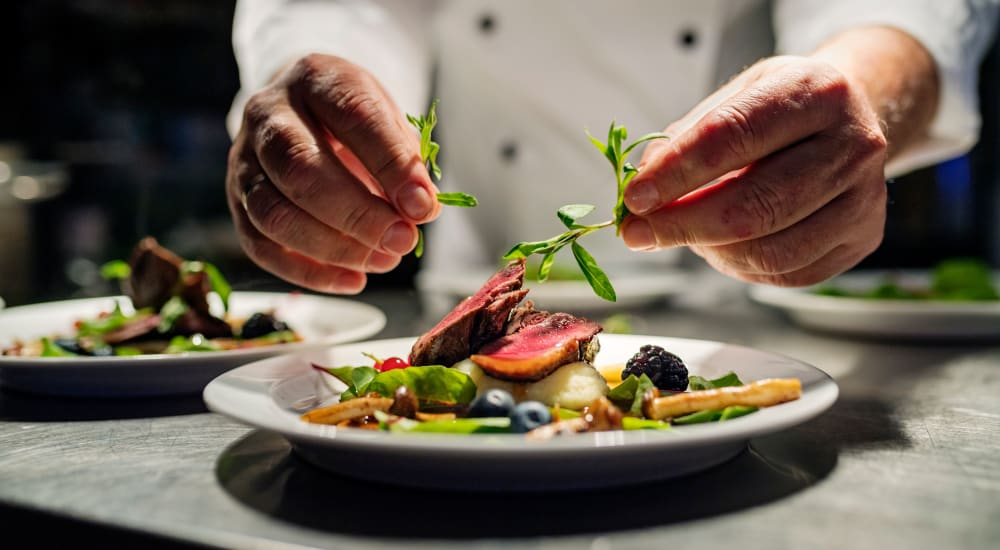 A chef topping a dish with garnish at The Springs at Greer Gardens in Eugene, Oregon