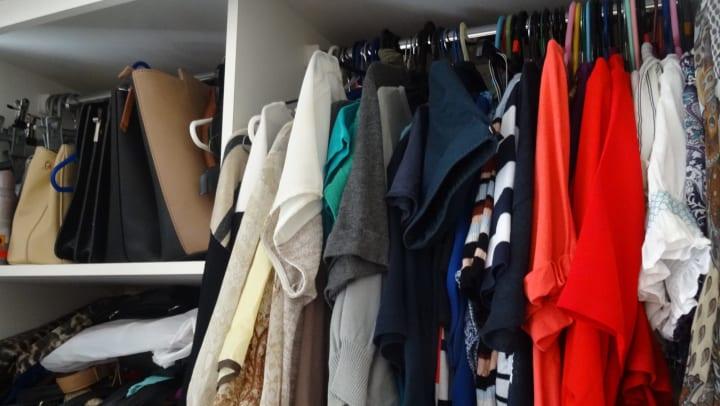 A messy closet full of clothing and handbags.