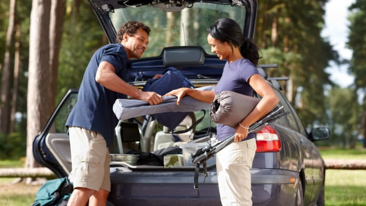 Man and woman removing camping gear from car.