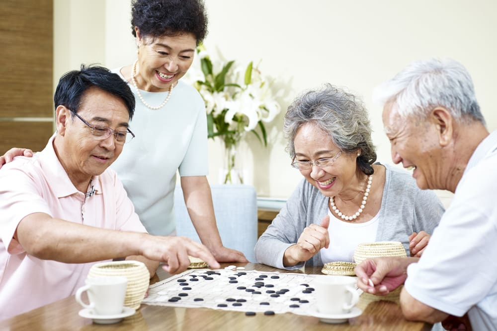 Two couples playing the Chinese game Go at Holden of Bellevue in Bellevue, Washington