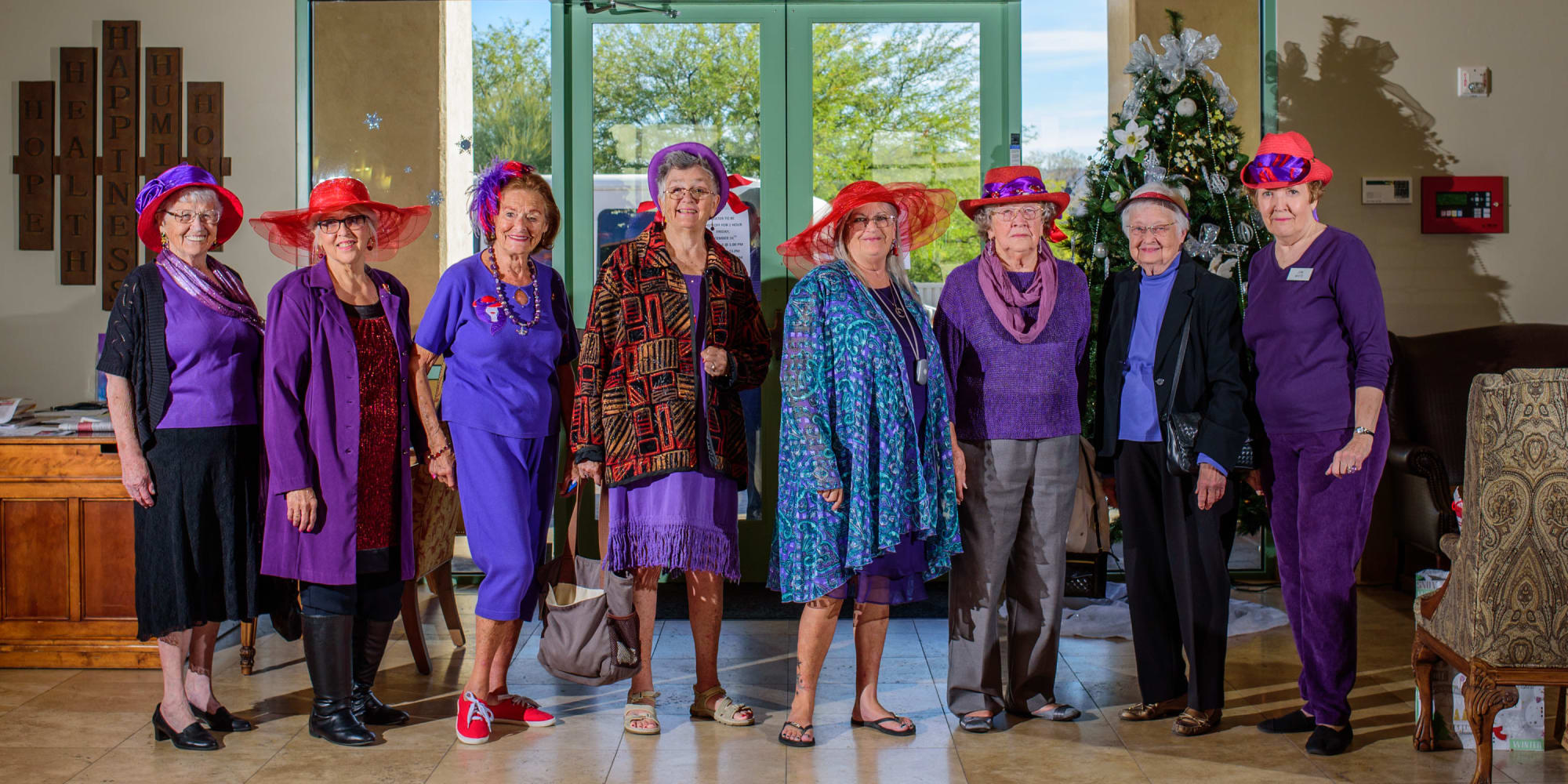 A  group of senior women wearing red hats from The Peaks at Santa Rita in Green Valley, Arizona in front of a plane