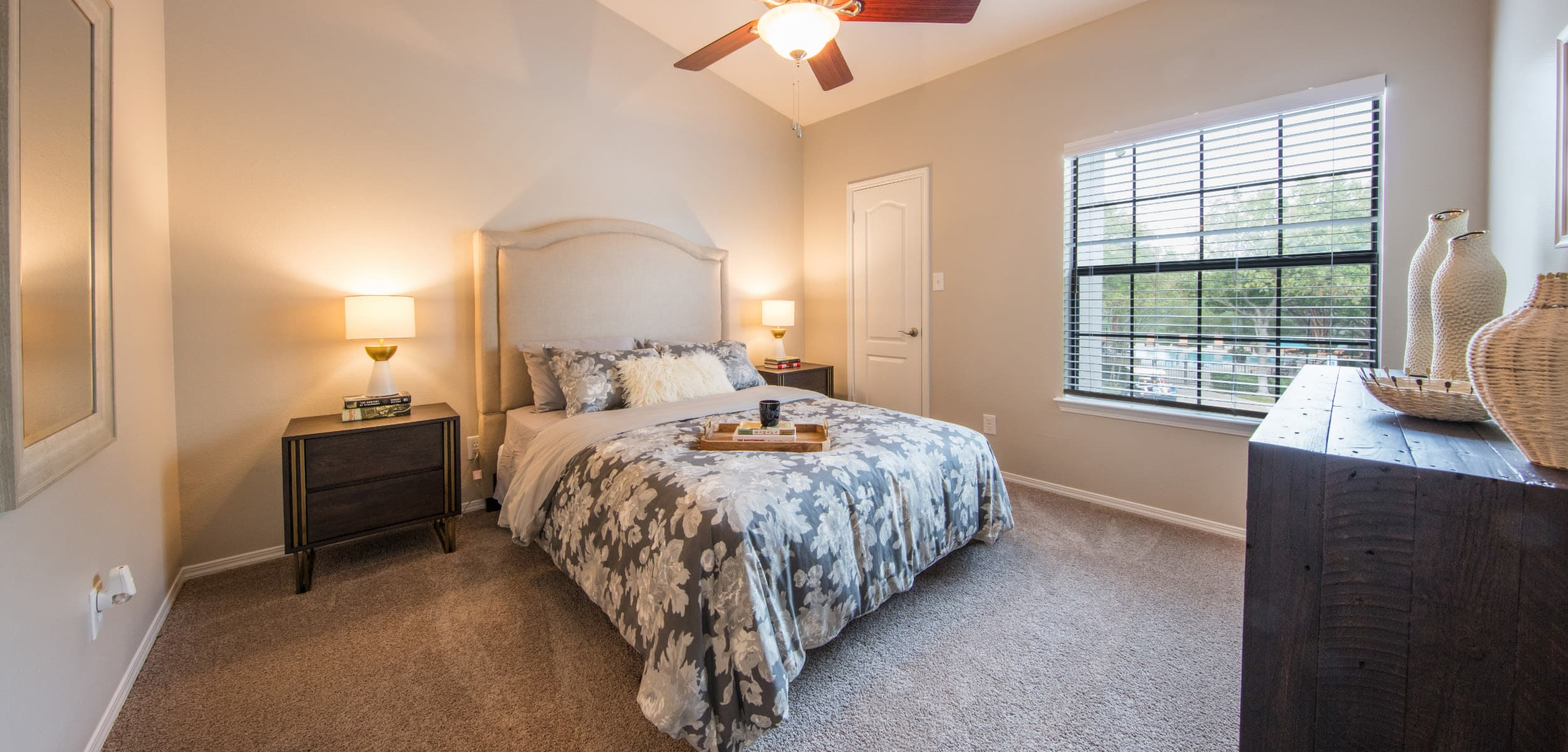 Bedroom with a large window at Marquis at Treetops in Austin, Texas