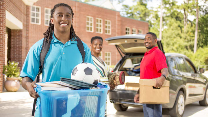 A male college student is holding a move-in bin. His parents are behind him in the background, both holding move-in items.