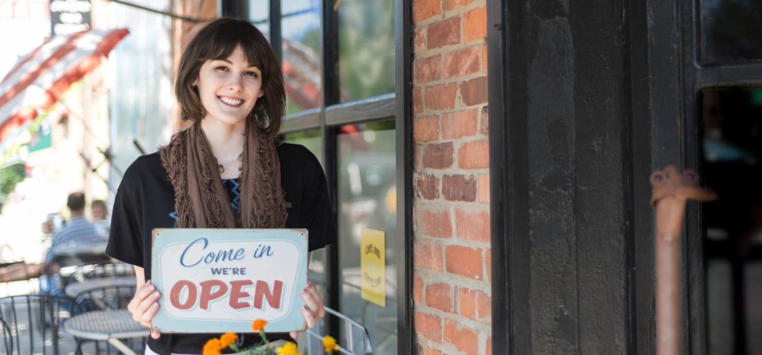Woman with open sign in front of business in Chapel Hill , NC near Alta Blu