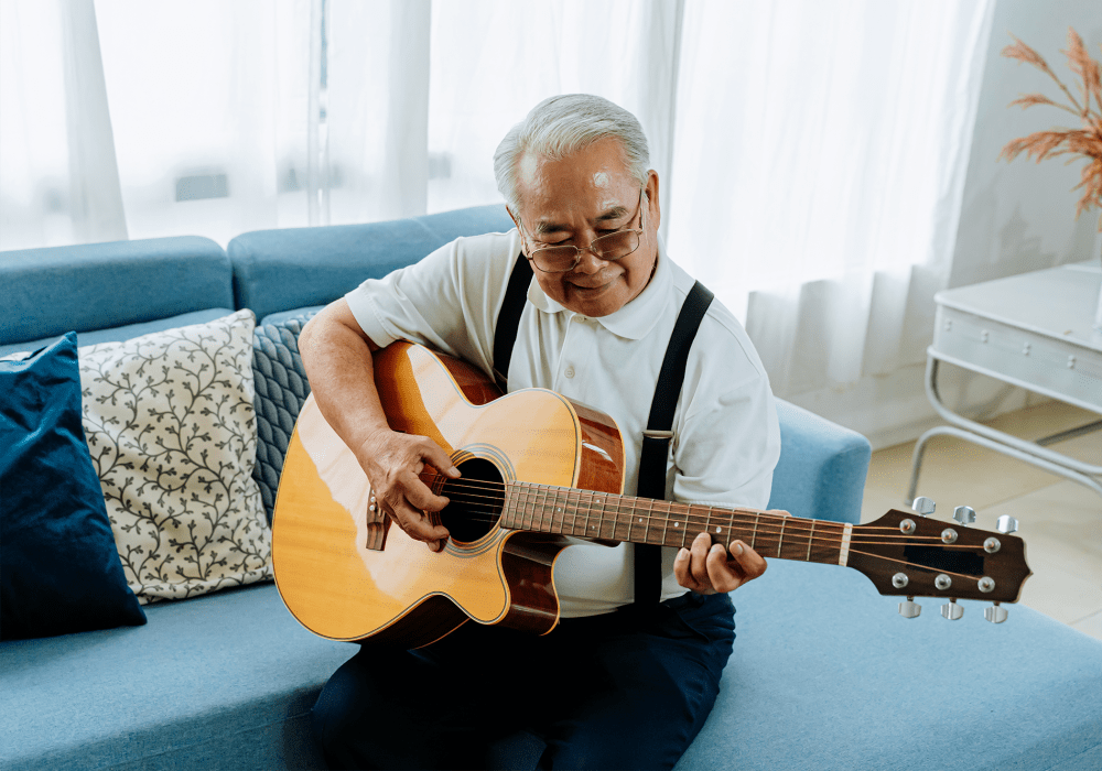 Resident sitting on a couch and playing an acoustic guitar at Sunstone Village in Denton, Texas