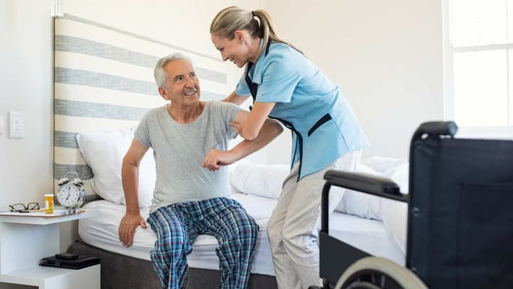Caregiver helping senior man out of bed