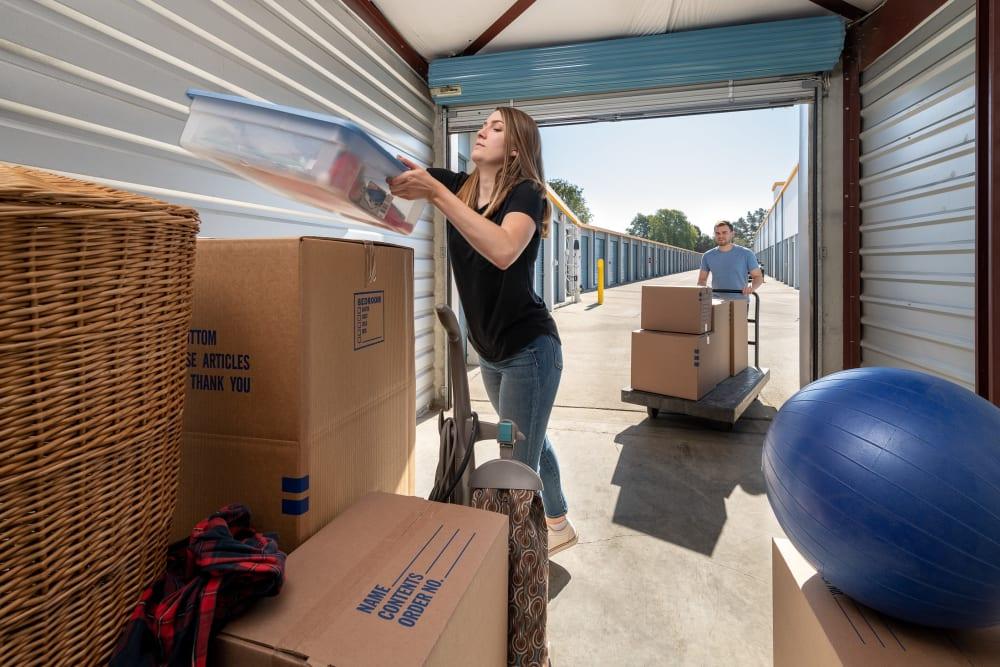 A woman organizing her storage unit at Castro Valley Hayward Storage LLC in Castro Valley, California