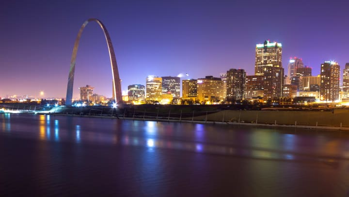 A picture of the St. Louis city skyline at night, featuring the Golden Arch