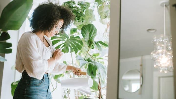 Women watering her plants in her home at Olympus Fenwick Apartments in Savannah, Georgia