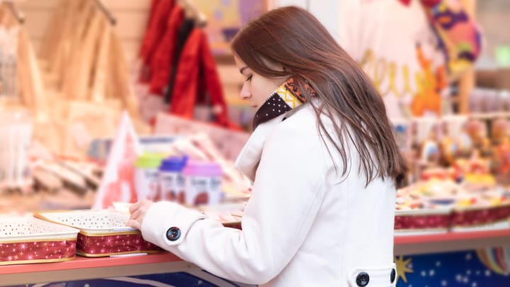 A young woman looking at a row of holiday gifts in a store.