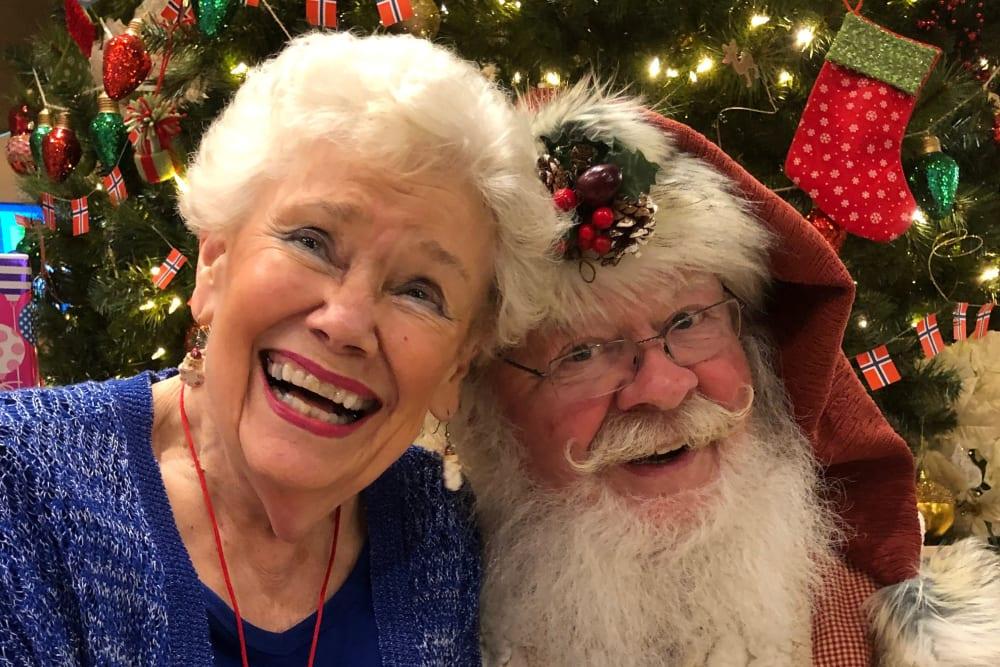 Senior resident taking a photo with Santa Claus at Merrill Gardens at Ballard in Seattle, Washington
