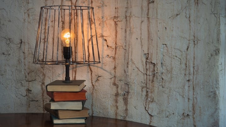 Lamp made from a stack of books and a bulb with iron shade.