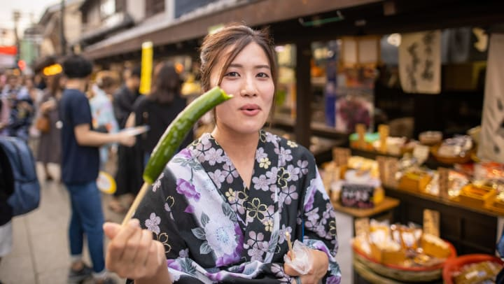 Woman on street eating a pickle on a stick.