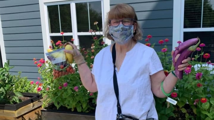 Woman-outside-with-mask-in-summer-holding-vegetables-in-garden