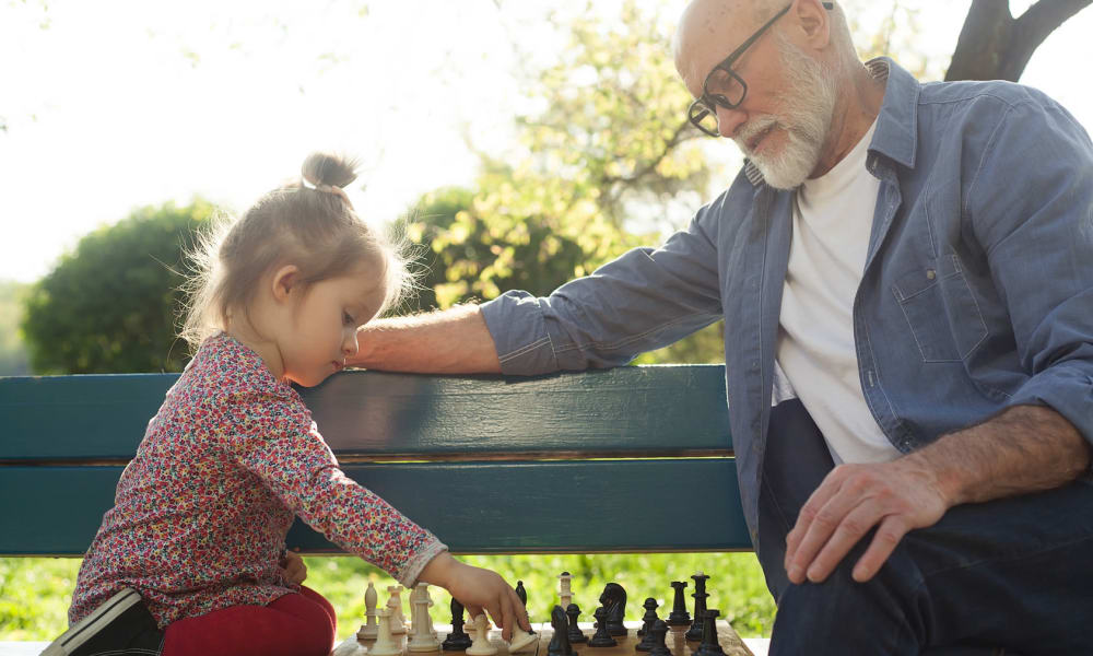 A resident from Touchmark at Coffee Creek in Edmond, Oklahoma playing chess with a child