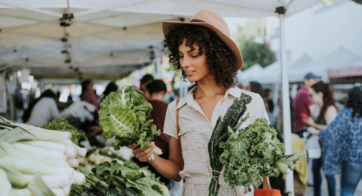 Resident shopping for fresh produce at a farmers' market near Mediterranean Village Apartments in Costa Mesa, California