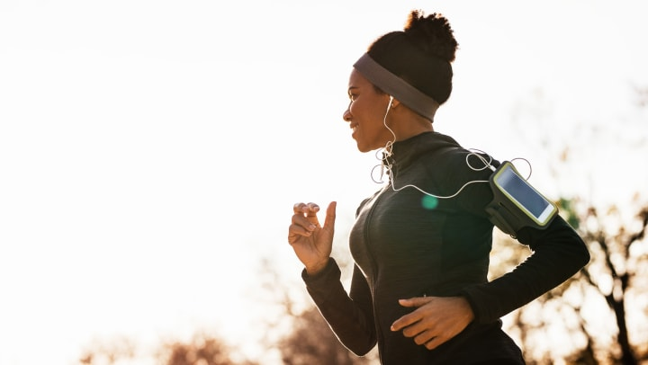 Woman happily running listening to music near Wimberly at Deerwood